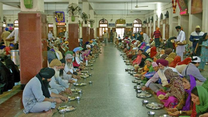 People eating in main hall Amritsar - Brightness modified